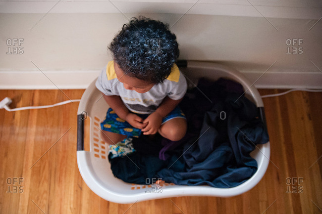 Boy sitting in a laundry basket with clothes