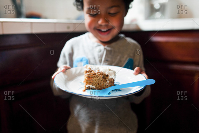 Boy holding plate with piece of cake and smiling