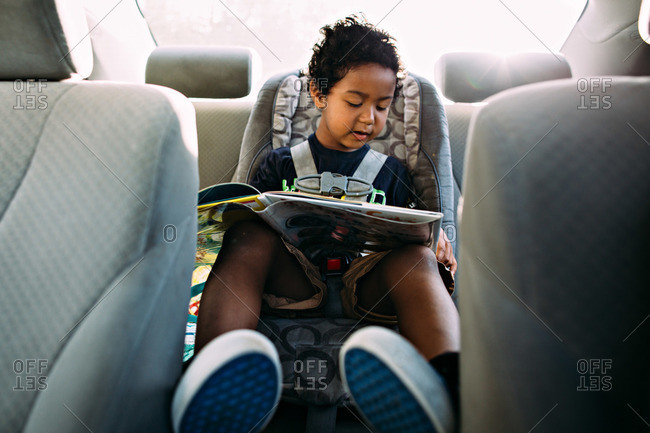 Little boy reading book while traveling in car