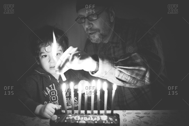 Child and grandfather lighting Hanukkah candles