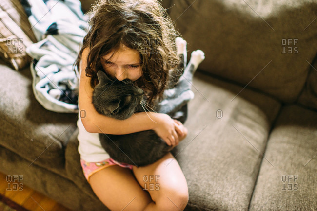 A girl gives a cat a kiss