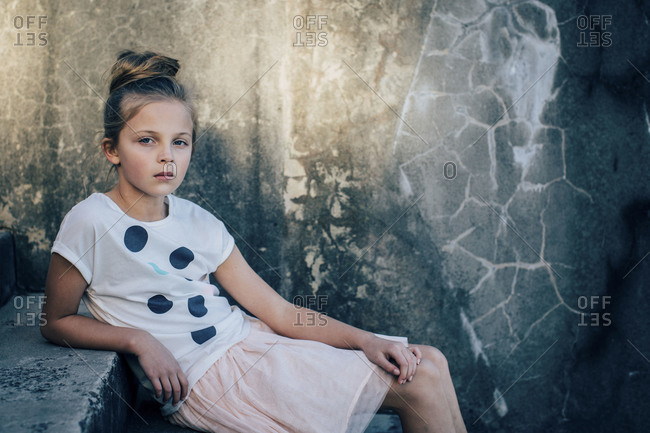 Portrait of young girl sitting on concrete steps