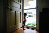 Two kids looking out front door together stock photo - OFFSET