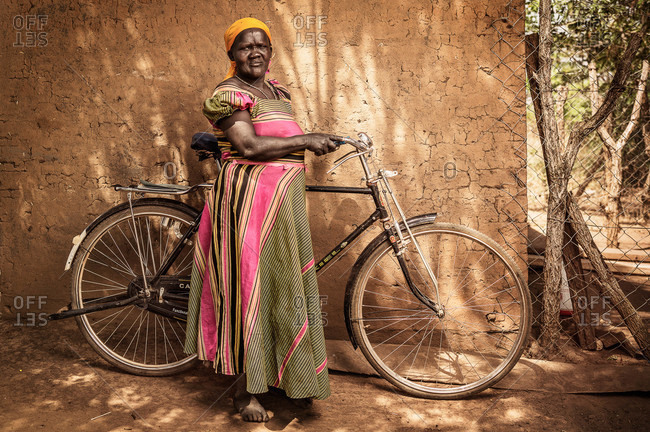 Paicho, Uganda - February 27, 2015: Woman standing with a bicycle against a wall