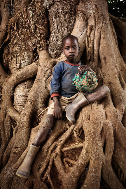Paicho, Uganda - February 27, 2015: Boy sitting on tree roots holding a ball