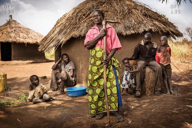 Paicho, Uganda - February 27, 2015: Ugandan woman and her family outside of a traditional home