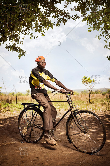 Oroko, Uganda - March 2, 2015: Young man sitting on a bicycle