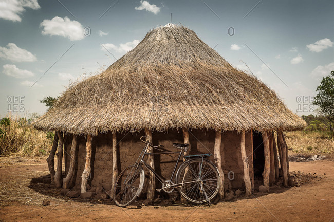 Bicycle leaning against a round hut with a thatched roof