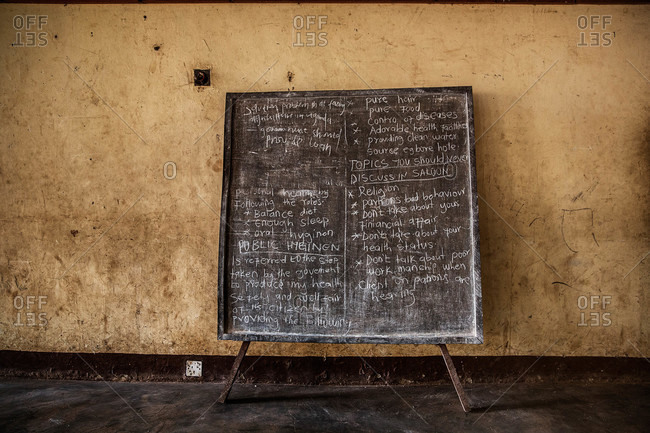 Slate with chalk handwriting about issues in Uganda
