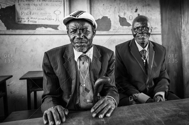 Paicho, Uganda - February 28, 2015: Senior men in suits sitting at a table