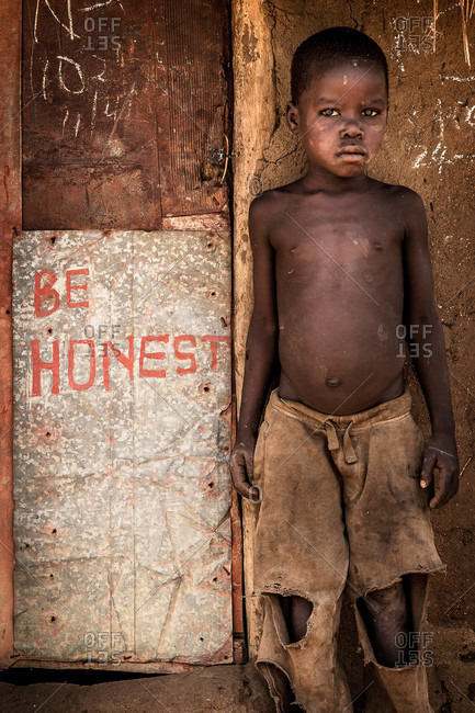 """Oroko, Uganda - March 2, 2015: Little boy standing in front of a hand-painted """"be honest"""" sign"""