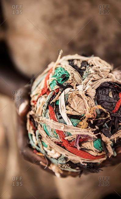 Boy holding a homemade ball made of cloth pieces