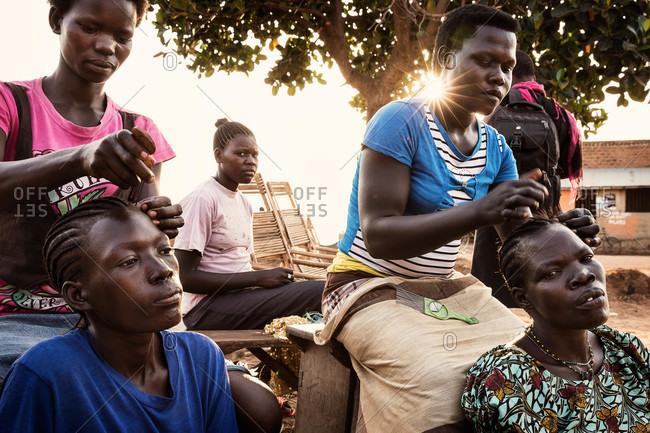 Palaro, Uganda - March 2, 2015: Women sitting and braiding each other's hair