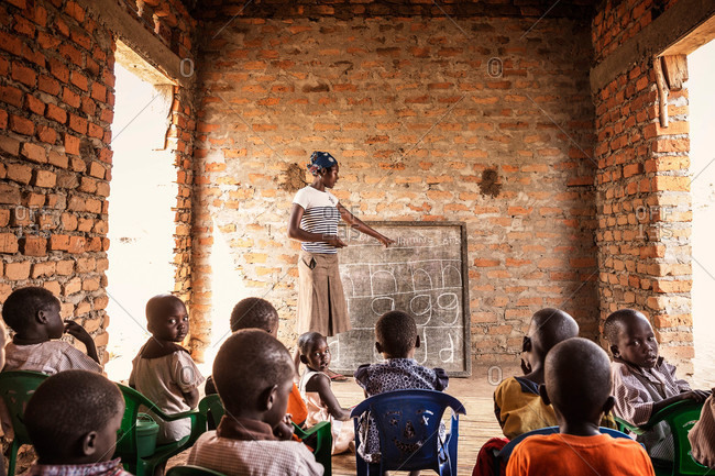 Paicho, Uganda - March 4, 2015: Woman teaching students letters on a chalkboard