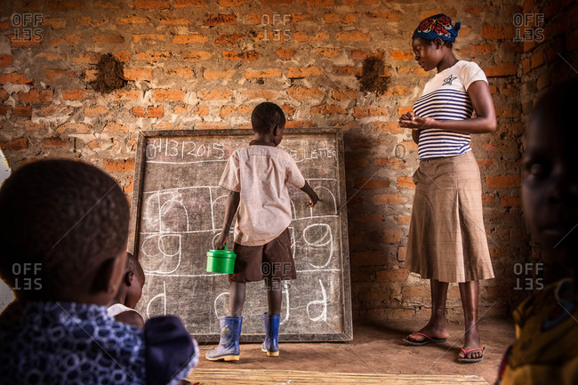 Paicho, Uganda - March 4, 2015: Boy standing at a classroom chalkboard pointing to letters