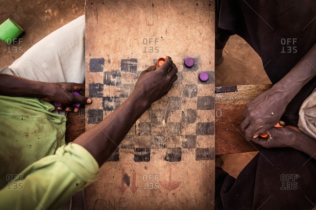 Two men playing checkers on a hand-painted board and bottlecaps