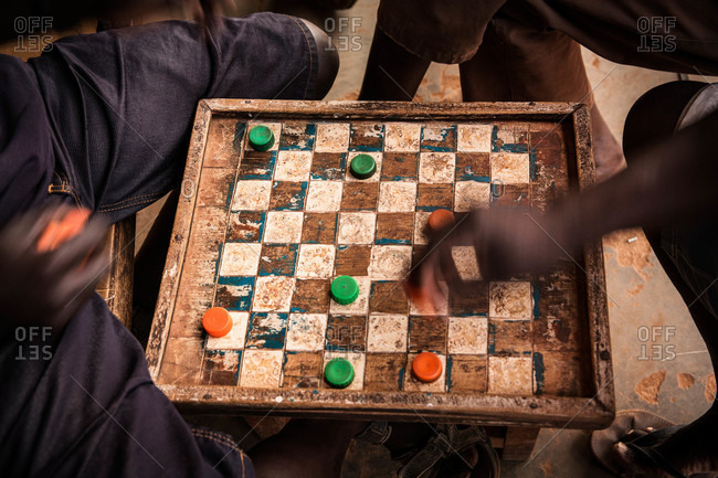Men playing a game of checkers on a worn board with bottlecaps