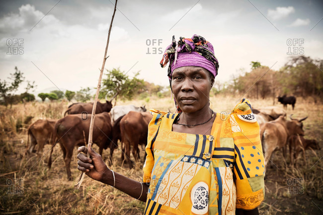 Paicho, Uganda - March 5, 2015: Woman standing in a field with cattle