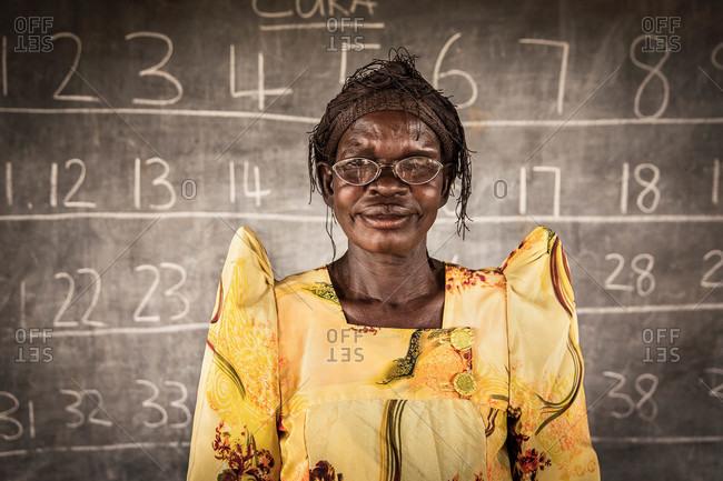 Mede, Uganda - March 5, 2015: Ugandan student standing in front of a chalkboard