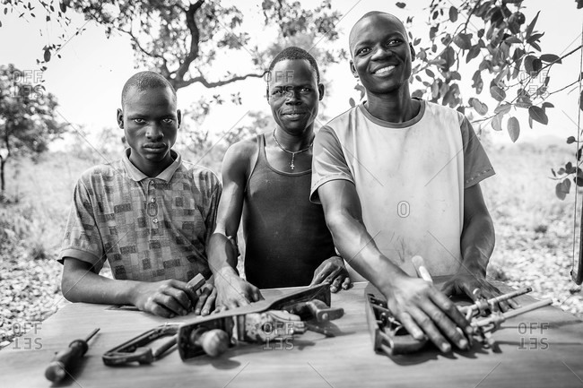 Paicho, Uganda - March 5, 2015: Three young men with woodworking tools