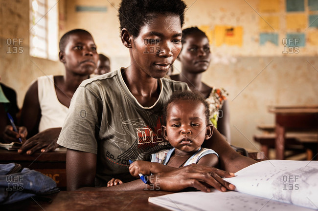 Paicho, Uganda - March 5, 2015: Young mother with her baby in a classroom looking at a textbook
