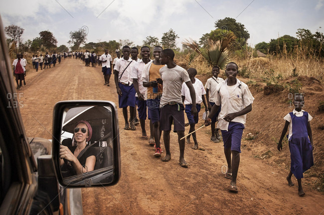 Paicho, Uganda - March 5, 2015: Ugandan students standing on the side of a road as a vehicle drives through