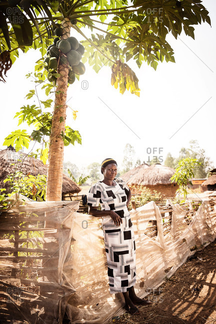 Lacor, Uganda - March 5, 2015: Woman leaning against a fence under a palm tree