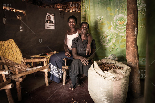 Lacor, Uganda - March 6, 2015: Two women sitting together in front of a large sack of peanuts