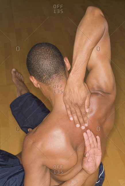 Athletic man stretching his back indoors