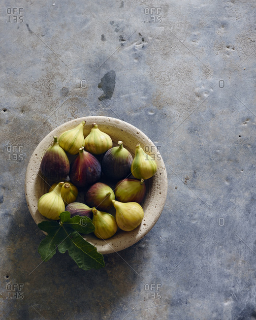 Overhead view of fresh figs in a bowl with a fig leaf