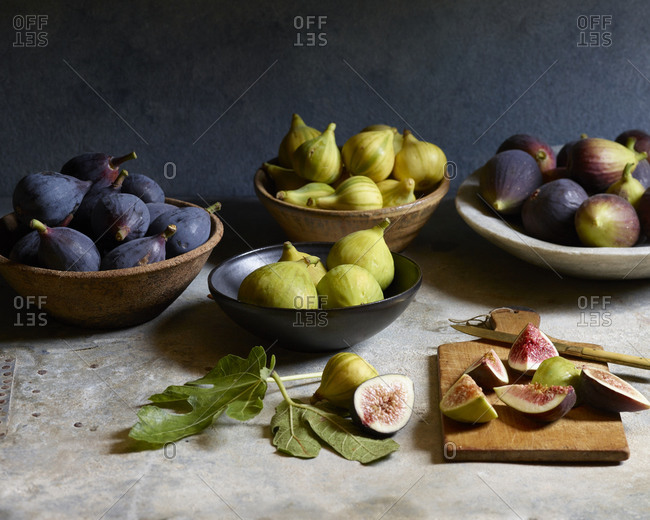 Still life of fresh figs in bowls with sliced figs on cutting board