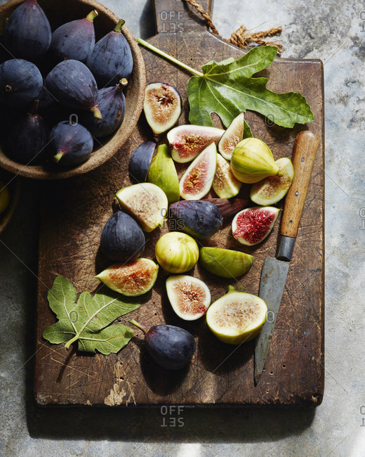 Overhead view of sliced figs on cutting board with whole figs in bowls