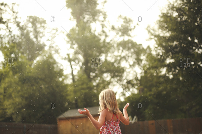 Young girl with her arms raised to feel a sudden summer rain shower