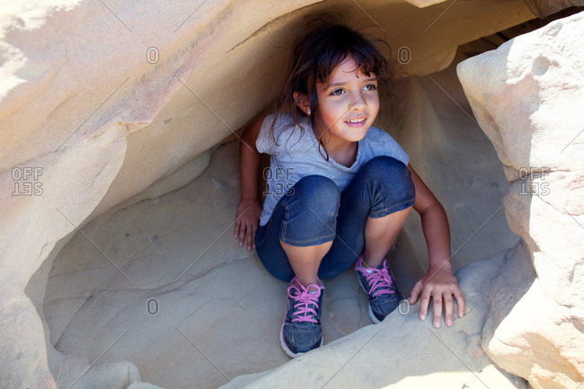 Girl playing inside rock crevices