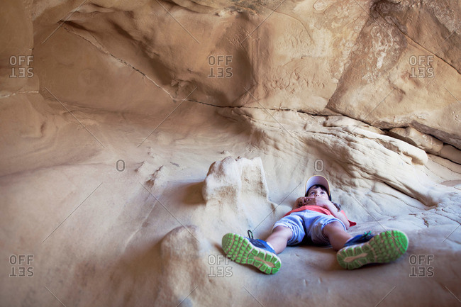 Boy resting inside a sandstone cave