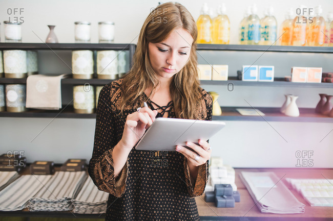 Boutique owner using tablet computer to review inventory