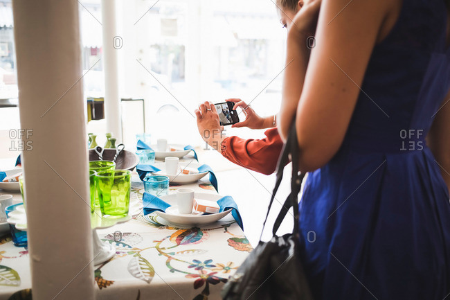 Woman taking pictures of products on display in a boutique