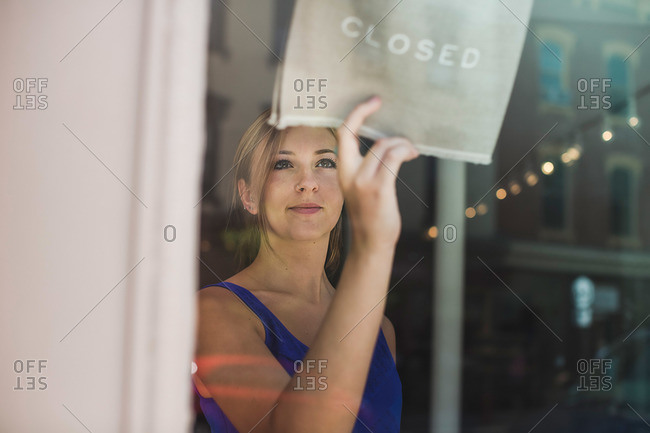 Shop worker putting a closed sign in window