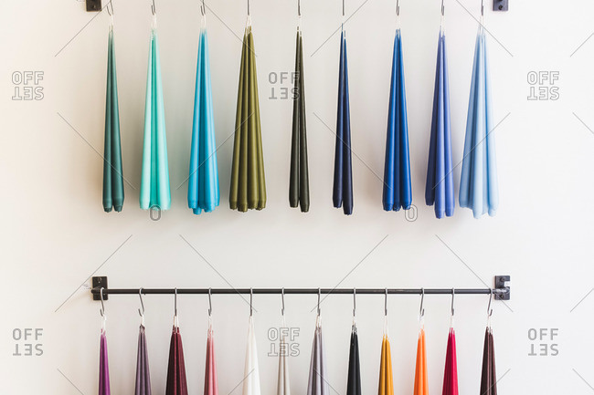 Candle tapers in different colors hanging from display in boutique