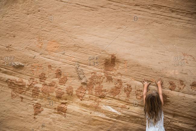 A girl creates muddy handprints on the walls of Bryce Canyon, Utah