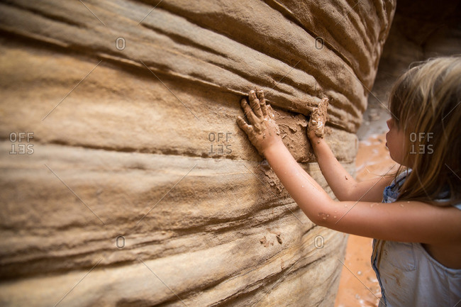 A girl spreads mud on a canyon wall in Bryce Canyon, Utah