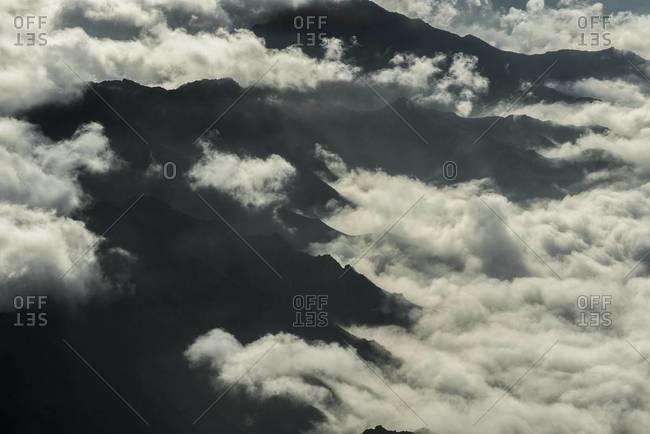 Mountain range peaking through clouds