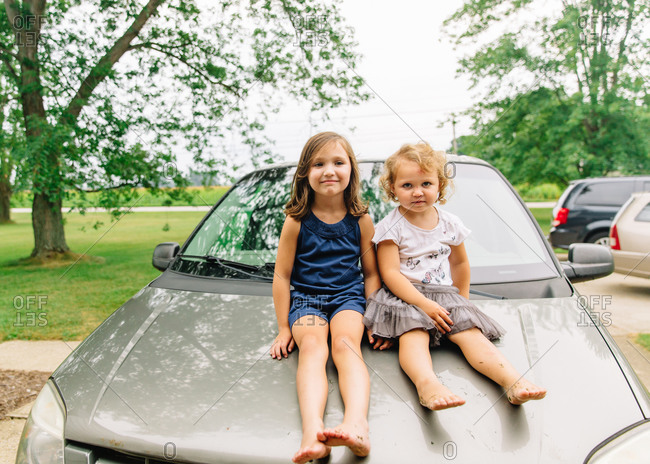 Sisters sitting on the hood of a car