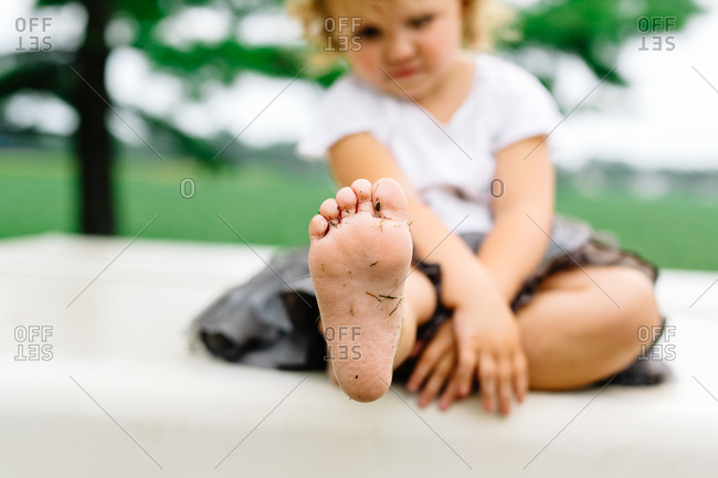 Little girl sitting with her foot extended