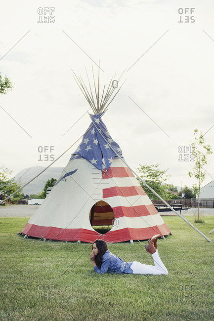 Woman lying on ground by American flag covered teepee