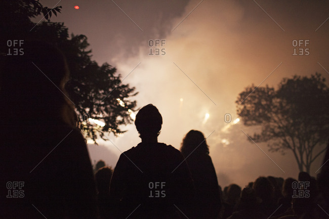 Silhouettes of people watching fireworks display