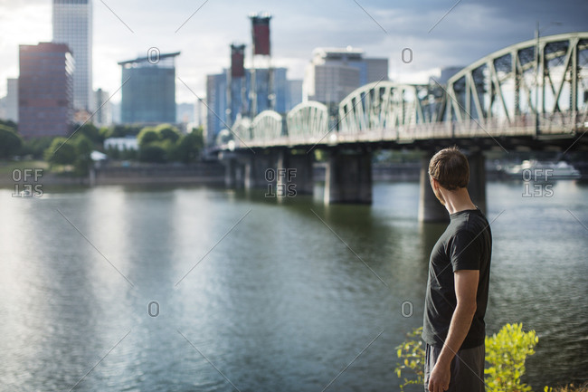 Man in workout clothes looking across city river