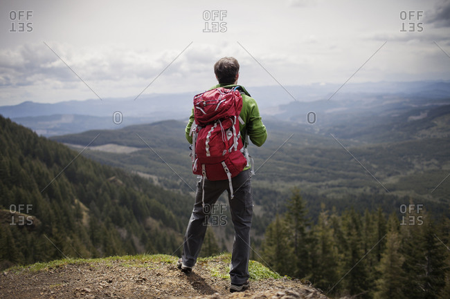 Man in backpack looking over expansive mountain valley