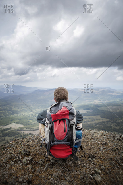 Man in backpack looking at expansive mountain valley
