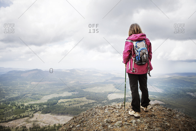 Woman in backpack looking over expansive mountain valley